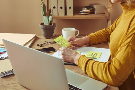 cropped image of woman holding sticker with idea word at table at home