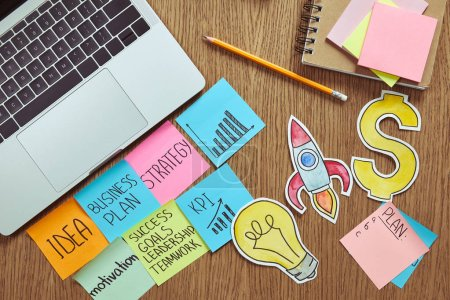 elevated view of paper stickers with business plan, paper signs and laptop on table at home