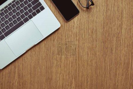 Foto de Vista superior del ordenador portátil, smartphone con pantalla en blanco y gafas en tablero de madera - Imagen libre de derechos