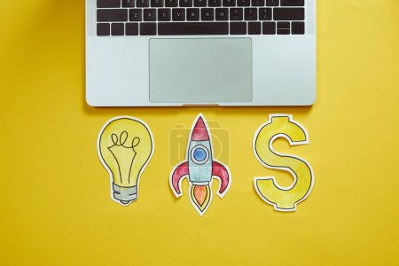 top view of laptop, paper lightbulb, paper rocket and dollar sign on yellow surface