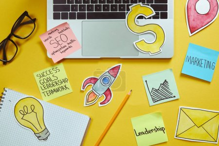 top view of laptop, paper signs and paper stickers with business plan on yellow surface