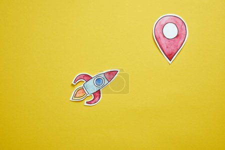 top view of paper rocket and location sign isolated on yellow