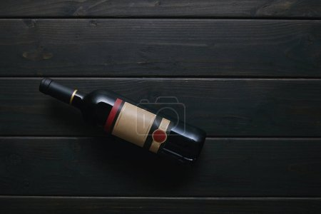 top view of single wine bottle with blank label on wooden surface