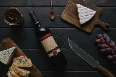 top view of wine bottle with blank label, knife and delicious snacks on wooden table