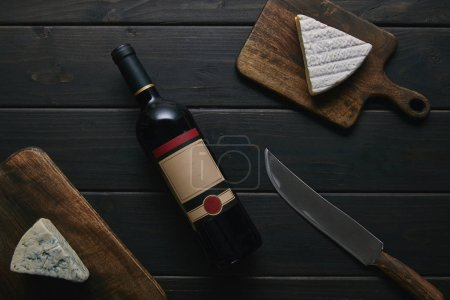 top view of wine bottle with blank label, knife and delicious cheese on wooden table