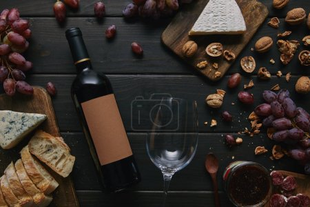 top view of wine bottle with blank label, glass and various delicious snacks on wooden table