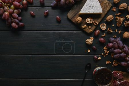 Photo for Top view of fresh ripe grapes, walnuts, sliced salami, jam and delicious cheese on wooden background - Royalty Free Image