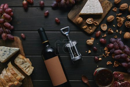 top view of wine bottle with blank label, corkscrew and various delicious snacks on wooden table