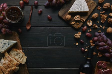 Photo for Top view of wine bottle and various delicious snacks on wooden table - Royalty Free Image