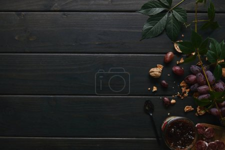 Photo for Top view of fresh ripe grapes, walnuts, green leaves, jam and sliced salami on wooden table - Royalty Free Image