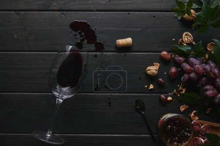top view of glass with red wine, cork and grapes with nuts on wooden surface