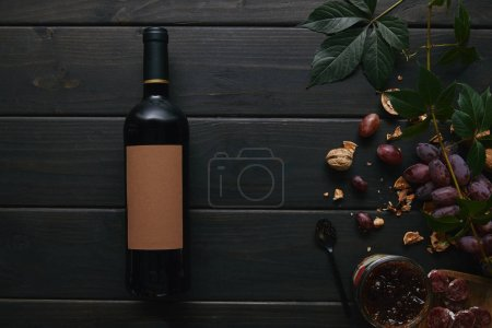 top view of wine bottle with blank label, grapes, nuts and jam on wooden surface