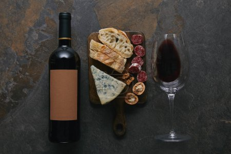 Photo pour Vue du dessus de la bouteille et du verre de vin rouge et délicieuses collations sur la planche à découper - image libre de droit