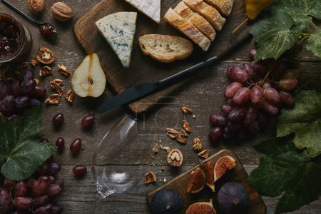 Photo pour Vue du dessus du verre à vin vide, des fruits frais et de délicieuses collations sur une table en bois - image libre de droit