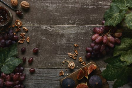 top view of sliced figs on cutting board, fresh ripe grapes, jam and walnuts on wooden table