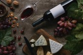 top view of bottle and glass of red wine, delicious cheese and grapes on wooden table
