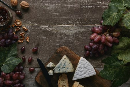 Photo for Top view of fresh ripe grapes with green leaves, walnuts, delicious  cheese and jam on wooden table - Royalty Free Image
