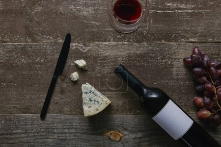 top view of wine bottle with blank label, glass with red wine, cheese, grapes and knife on wooden table