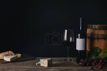 close-up view of glass, bottle and barrel of wine on wooden table