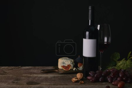 bottle and glass of red wine, grapes and cheese on wooden table