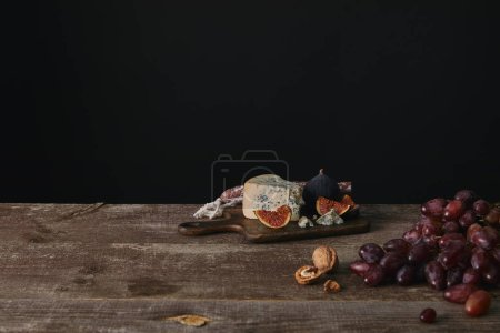 fresh ripe grapes, nuts and delicious cheese on wooden table on black