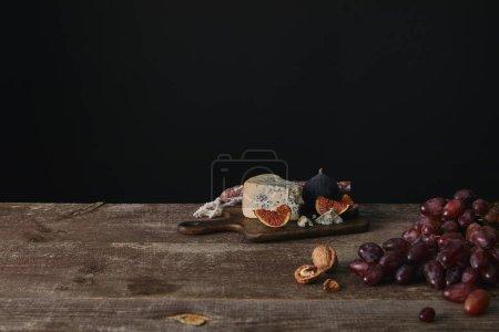 les raisins mûrs frais, noix et fromage délicieux sur la table en bois sur fond noir