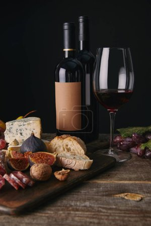 close-up view of bottles and glass of red wine, fruits and delicious cheese on wooden table