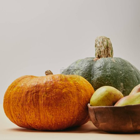 autumnal harvest with pumpkins and ripe tasty pears on tabletop