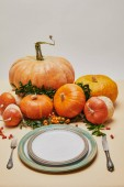 plates, fork, knife and pumpkins with firethorn berries on table