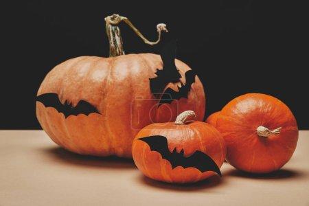 three orange halloween pumpkins with paper bats on tabletop