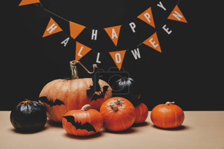 pumpkins, paper bats and paper garland with words happy halloween