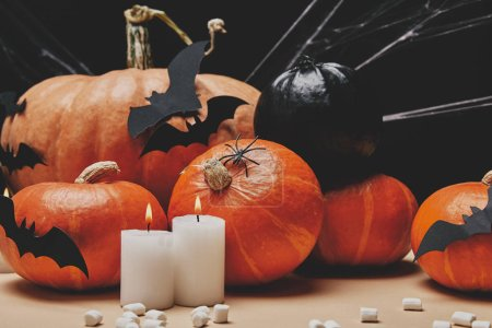candles with flame, pumpkins, paper bats and scattered marshmallows on table, halloween concept