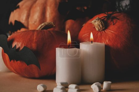 candles with flame, pumpkins and paper bats on table, halloween concept