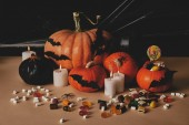halloween still life with pumpkins, sweets and decoration on tabletop