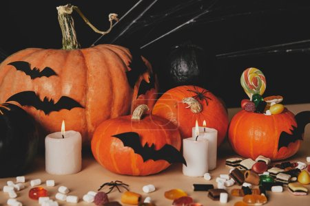 pumpkins, jelly candies, marshmallows and paper bats on table, halloween concept