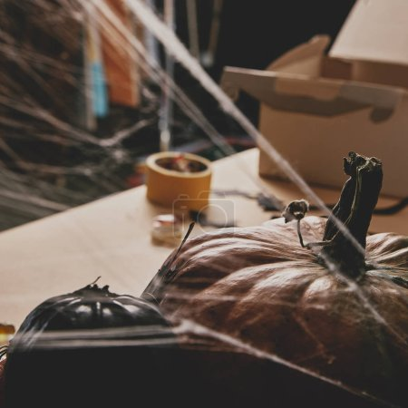 pumpkins and spiderweb on table, halloween concept