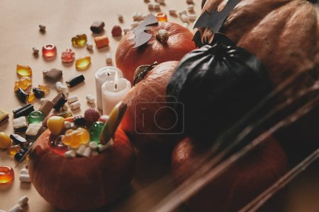 high angle view of halloween pumpkins, jelly candies and paper bats on table