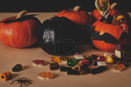 pumpkins, tasty jelly candies and paper bats on tabletop, halloween concept