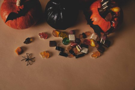 high angle view of pumpkins, paper bats and jelly candies on table, halloween concept