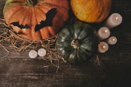 elevated view of pumpkins, candles and paper bats on table, halloween concept