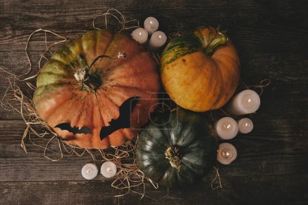 top view of pumpkins, candles and paper bats on table, halloween concept