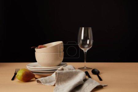 Photo pour Assiettes, bols, verre à vin, serviette et poires sur table beige - image libre de droit
