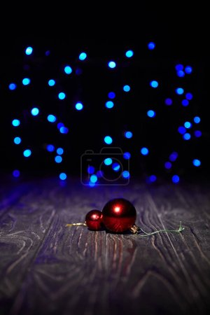 red christmas balls on wooden table with blue sparkling background