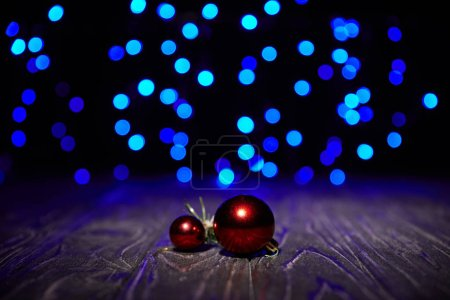 red christmas balls on wooden table with blue shiny background