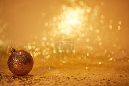 golden glossing christmas ball for decoration on glittering tabletop