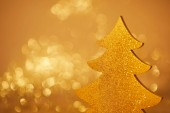 golden glittering christmas tree for decoration on blurred background
