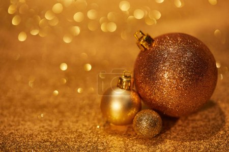 golden shiny decorative christmas balls on tabletop with sequins