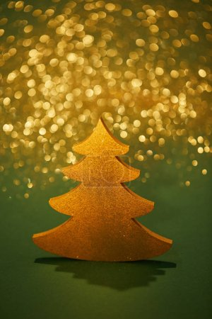 golden glittering christmas tree for decoration on green background