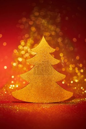 beautiful golden glittering christmas tree for decoration on red background