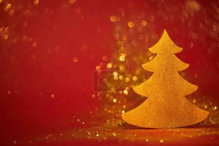 golden glittering decorative christmas tree on red background